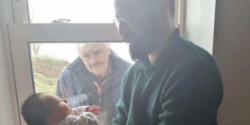 Ο παππούς κοιτάζει <br> το νεογέννητο εγγόνι <br> πίσω από το τζάμι